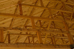 Part of the wooden architecture of the building interior. The wood-paneled ceiling with wooden beams lining. stock image