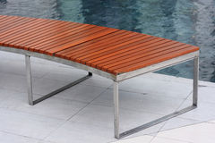 Part of wooden bench on steel frame near a pool Stock Photos