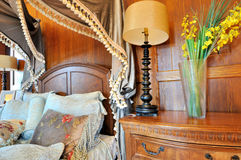 Part of wooden decorated bedroom. With fancy and elaborate style, and flowery curtain, shown as luxury, classical, and comfortable living environment Stock Photo