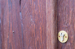 Part of the wooden door brown close-up with brass keyhole Royalty Free Stock Image