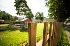 Part of the wooden fence on the background of the blurred kindergarten. Soft focus Royalty Free Stock Photos