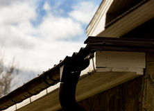 Part of a wooden house, roof and sky with clouds Royalty Free Stock Images