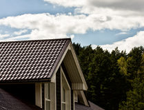 Part of a wooden house, roof and sky with clouds Stock Photo
