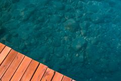 Part of the wooden pier and clear water sea water, visible stones stock image