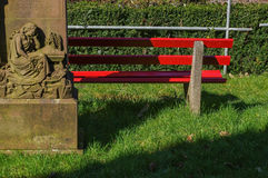 Part of wooden red park bench near a statue. A part of wooden red park bench near a statue Stock Images