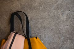 Part of yellow leather female bag on grey wall backgroud stock image
