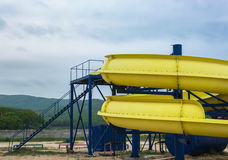 Part of a yellow waterslide on the beach Royalty Free Stock Photo