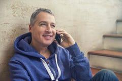 Partager de bonnes actualités Vue de côté de jeune homme beau parlant sur le téléphone portable et le sourire Photo libre de droits
