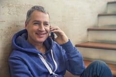Partager de bonnes actualités Vue de côté de jeune homme beau parlant sur le téléphone portable et le sourire Photographie stock
