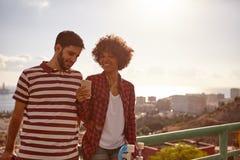 Partager des couples riant sur un pont Image libre de droits