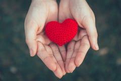 Partager la couleur rouge d'amour et de coeur sur la main de femmes Image stock