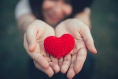 Partager la couleur rouge d'amour et de coeur sur la main de femmes dans le jour du ` s de valentine Images libres de droits