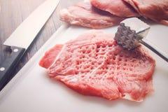 Parte amaciada de carne crua em uma placa de corte branca Imagens de Stock Royalty Free