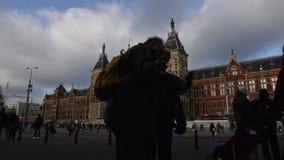 Parte anterior da estação central de Amsterdão com povos e os bondes moventes Lapso de tempo vídeos de arquivo