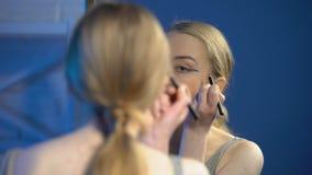 Parte anteriore d'applicazione femminile adolescente graziosa dell'eye-liner dello specchio, imparante fare trucco archivi video