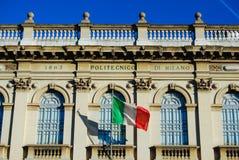 Parte anteriore della costruzione politecnica dell'università di Milano con la bandiera italiana immagine stock