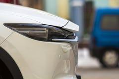 Parte anteriore della fine moderna bianca dell'automobile su fotografia stock