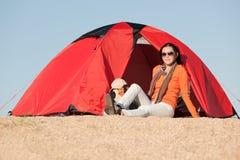 Parte anteriore di seduta di campeggio della donna felice della tenda fotografia stock