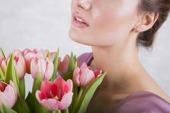 Parte da cara bonita do ` s da moça com o ramalhete cor-de-rosa das tulipas Fotografia de Stock Royalty Free