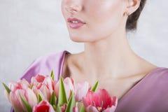 Parte da cara bonita do ` s da moça com o ramalhete cor-de-rosa das tulipas Imagens de Stock Royalty Free