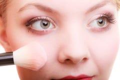 Parte da cara da mulher que aplica o detalhe da composição do ruge do vermelho Foto de Stock