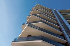 Parte da construção moderna da arquitetura Prédio de escritórios moderno do centro de negócios com a fachada de concreto reforçad fotografia de stock