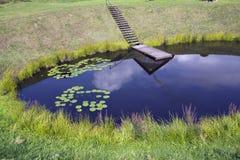 Parte da lagoa redonda perfeita da vila com os lírios da ponte e de água Imagem de Stock Royalty Free