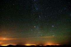 Parte da maneira leitosa sobre luzes e montanhas da cidade Foto de Stock