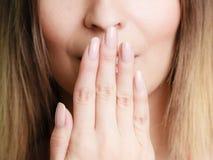 Parte da mulher da cara que cobre sua boca com a mão imagem de stock royalty free
