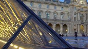 Parte da pirâmide iluminada, turistas que andam perto do palácio do Louvre no fundo video estoque