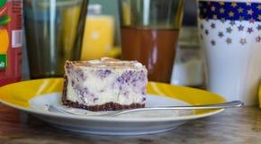 Parte da torta de mirtilo em uma placa, vidros no fundo imagens de stock royalty free