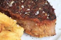 Parte de bife com close-up das batatas fritas Fotos de Stock Royalty Free