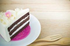 Parte de bolo de chocolate com a flor no fundo de madeira imagens de stock royalty free