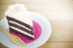 Parte de bolo de chocolate com a flor no fundo de madeira fotos de stock