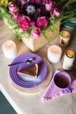 Parte de bolo delicioso da musse de chocolate na placa colorida no fundo de madeira da tabela Ajuste da tabela com flores e velas Fotografia de Stock