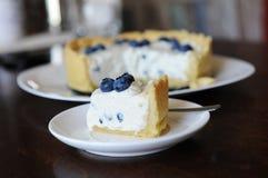 Parte de bolo de queijo com mirtilos em uma placa no foco no fundo do bolo de queijo inteiro Fotografia de Stock Royalty Free
