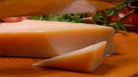 Parte de corte duro do queijo parmesão pela faca em uma placa de madeira filme