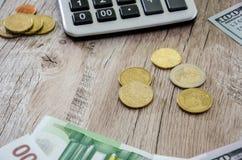 Parte de la calculadora, del euro, de los dólares y de las monedas en un fondo de madera imagenes de archivo