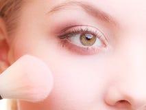 Parte de la cara de la mujer que aplica el detalle del maquillaje del colorete del colorete Fotos de archivo