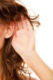 Parte de la mujer principal con la mano al oído que escucha Foto de archivo