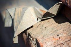 A parte de metal amarrotada está no tijolo imagens de stock royalty free