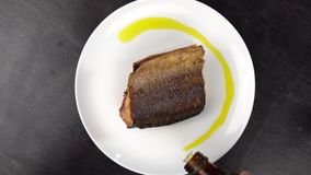 A parte de peixes vermelhos fritados na placa branca gerencie contra a tabela preta vídeos de arquivo