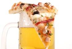 Parte de pizza na caneca de cerveja Fotografia de Stock Royalty Free