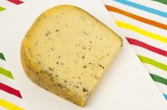 Parte de queijo holandês com ervas em uma placa de corte Foto de Stock Royalty Free