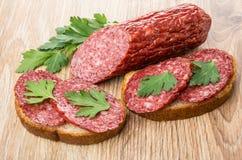 Parte de salsicha e de sanduíches com salsicha fumado e salsa Imagem de Stock