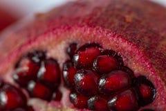 Parte de um close up suculento das sementes da romã Fundo bonito do granate vermelho das grões imagens de stock