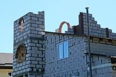 Parte de uma casa inacabado do tijolo cinzento com uma janela contra um céu azul imagem de stock