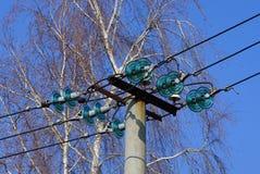 Parte de uma coluna concreta cinzenta com fios elétricos contra um céu azul e ramos de árvore fotos de stock royalty free