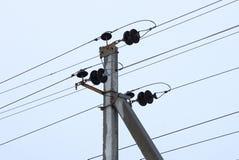 Parte de uma coluna concreta cinzenta com fios pretos contra o céu fotografia de stock