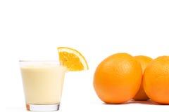 Parte de uma laranja em um milkshake alaranjado em o dianteiro Fotos de Stock Royalty Free